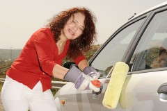 a woman painting a car with a paint roller