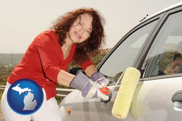 a woman painting a car with a paint roller - with Michigan icon