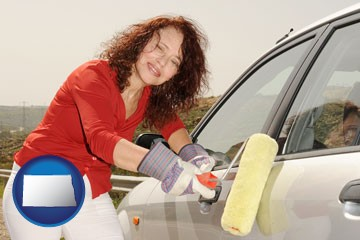 a woman painting a car with a paint roller - with North Dakota icon